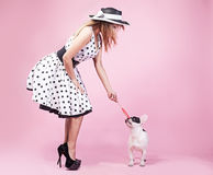 Pinup woman with pug dog. Pinup fashionable woman posing with cute pug dog. Pink background stock photos