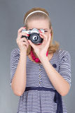 Pinup woman in retro clothes posing with photo camera Stock Photos