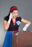 Pinup woman with retro suitcase and phone Royalty Free Stock Photography