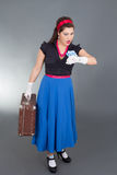 Woman with retro suitcase looks at the clock Stock Photography