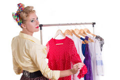 Pinup woman showing dresses on hanger Royalty Free Stock Photos