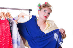 Pinup woman showing dresses on hanger looking up Stock Photography