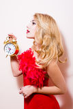 Pinup woman showing golden alarm clock at 10.30 Royalty Free Stock Images