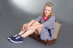 Pinup woman sitting in big brown retro suitcase Stock Images