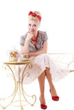 Pinup woman sitting at tea table Stock Images