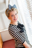 Pinup young woman having fun on the balcony. Closeup image of pinup girl beautiful blond young woman in striped blouse having fun happy smiling looking  in Royalty Free Stock Photos