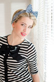 Pinup young woman having fun on the balcony. Closeup image of pinup girl beautiful blond young woman in striped blouse having fun happy smiling looking  in Royalty Free Stock Photography