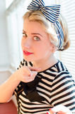 Pinup young woman having fun on the balcony. Closeup image of pinup girl beautiful blond young woman in striped blouse having fun happy smiling looking  in Stock Image