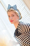 Pinup young woman having fun on the balcony. Closeup image of pinup girl beautiful blond young woman in striped blouse having fun happy smiling looking  in Stock Photography