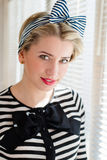 Pinup young woman having fun on the balcony. Closeup image of pinup girl beautiful blond young woman in striped blouse having fun happy smiling looking  in Royalty Free Stock Image