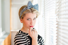 Pinup young woman having fun on the balcony. Closeup image of pinup girl beautiful blond young woman in striped blouse having fun happy smiling looking  in Royalty Free Stock Images