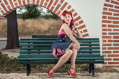Pinup young woman in vintage style clothing. View of pinup young woman in vintage style clothing  sitting on bench on a park Royalty Free Stock Photos
