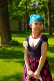 Pinup young woman witch blue hair in vintage style clothing in city park Stock Image