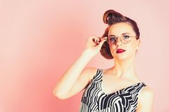 Pinup, youth and look. Beauty and fashion, teacher. Girl in stylish vintage dress on pink. secretary, hairdresser and cosmetics. Woman with retro hair and royalty free stock photo