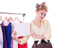 Pinupfrau, die leere Anmerkung über Aufhänger und Kleidern hält stockfotografie