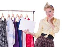 Pinupfrau, die leere Anmerkung über Aufhänger und Kleidern hält lizenzfreies stockfoto