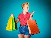 Pinupmädchen mit den Einkaufstaschen, die am Telefon texing sind stockfotos