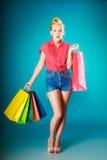 Pinupmädchen mit Einkaufstaschen Kleidung kaufend Verkauf stockfotografie