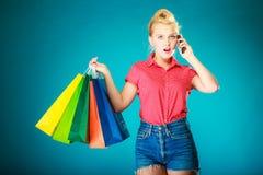 Pinupmädchen mit Einkaufstaschen um Telefon ersuchend Stockbilder