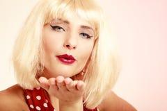 Pinupmädchen im Retro- Kleid der blonden Perücke, das einen Kuss durchbrennt Stockfotos