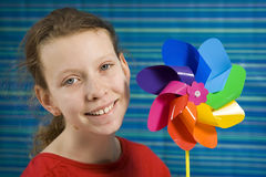 Pinwheel. Children with rainbow pinwheel on a striped blue background Royalty Free Stock Photos