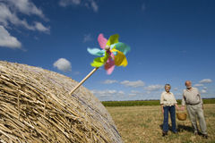 Pinwheel in bale of hay, couple with basket in background royalty free stock photo
