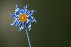 A pinwheel. Blue and white pinwheel over dark green effect Royalty Free Stock Photography