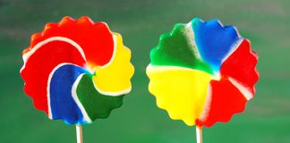 Pinwheel candy suckers. 2 large pinwheel candy suckers against a green background Stock Photo