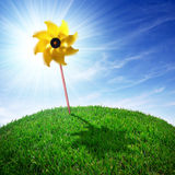 Pinwheel on Grass. Yellow, pinwheel on a round grass meadow at a bright sunny day Stock Image