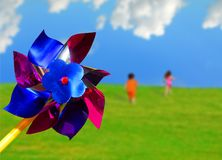 Pinwheel and Running Children. Colorful pinwheel toy with children running up grassy hill in background Royalty Free Stock Photos