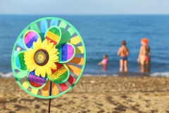 Pinwheel toy on beach, family standing in water. Multicolored pinwheel toy with flower on beach, family standing in water Royalty Free Stock Photo