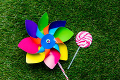 Pinwheel toy and lollipop candy on green grass background, Royalty Free Stock Photo