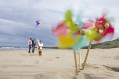 Pinwheels on beach, family with kite in background (blurred motion) Royalty Free Stock Photography