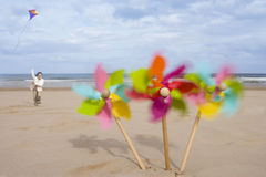 Pinwheels on beach, girl (5-7) flying kite in background (blurred motion) Stock Photo