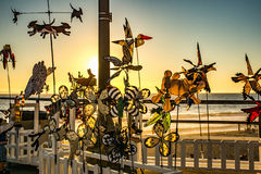 Pinwheels spinning on pier. At sunset at the beach in the summer Stock Image
