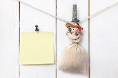 Pinza del muñeco de nieve de la Navidad que sostiene el saco y el papel de nota fijado Fotografía de archivo