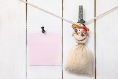 Pinza del muñeco de nieve de la Navidad que sostiene el saco y el papel de nota fijado Imagen de archivo