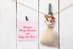 Pinza del muñeco de nieve que lleva a cabo la nota del saco y del saludo de la Navidad Foto de archivo libre de regalías