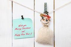 Pinza del muñeco de nieve que lleva a cabo la nota del saco y del saludo de la Navidad Fotografía de archivo libre de regalías