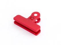 Pinza plástica roja de la talla media para las bolsas de plástico aisladas en un fondo blanco Fotografía de archivo libre de regalías