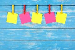 Pinzas coloreadas en una cuerda con cinco tarjetas Imágenes de archivo libres de regalías