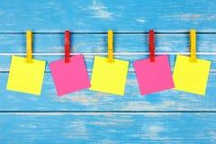 Pinzas coloreadas en una cuerda con cinco tarjetas Imagen de archivo