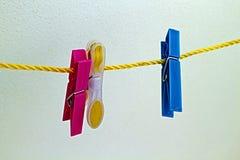 Pinzas coloreadas que cuelgan de un hilo Imagenes de archivo