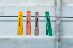 Pinzas coloreadas viejas que cuelgan en un alambre para secar la ropa foto de archivo