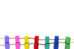 Pinzas coloridas en el fondo blanco Fotografía de archivo libre de regalías