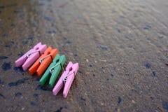 Pinzas coloridas en fondo mojado del roadcement Fotos de archivo