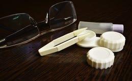 Pinzas de las lentes de los vidrios y lentes de los envases fotografía de archivo