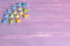 Pinzas de pelo azules, amarillas, verdes en fondo de madera de la lila con el espacio vacío para el texto Imágenes de archivo libres de regalías