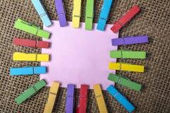 Pinzas en blanco de la nota y del color fotos de archivo libres de regalías