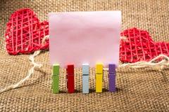 Pinzas en blanco de la nota y del color imágenes de archivo libres de regalías